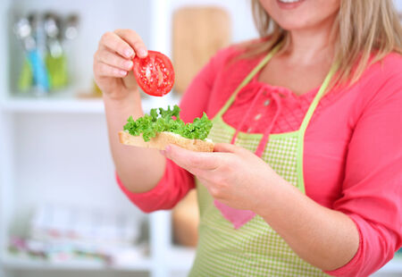Happy smiling woman in kitchen preparing  sandwich  photo