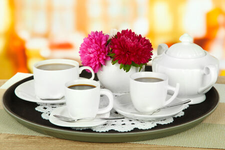 Cups of coffee on tray on table in cafe photo