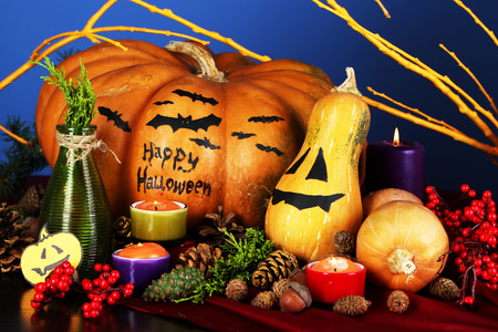 Composition for Halloween with pumpkins and candles on blue background photo