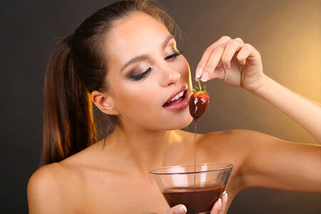 Portrait of beautiful young girl with strawberry in chocolate on brown background Stock Photo - 24350551