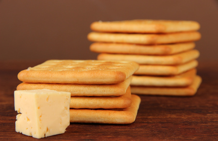 Delicious crackers with cheese on wooden table on brown background photo