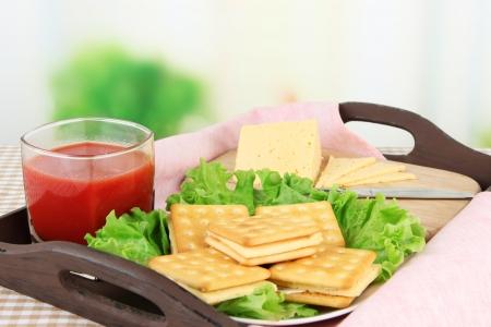 Sandwich crackers with cheese and tomato juice on tablecloth on bright background photo