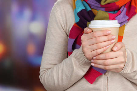 Hot drink in paper cup in hands on bright background photo