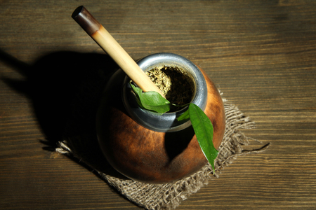 Calabash and bombilla with yerba mate on grey wooden background photo