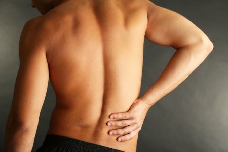 masaje deportivo: Hombre joven con dolor de espalda en gris
