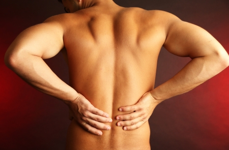 Young man with back pain on dark  Stock Photo - 22903644