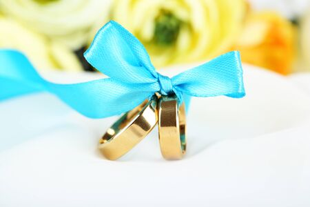 wedding accessories: Wedding rings tied with ribbon on white fabric Stock Photo