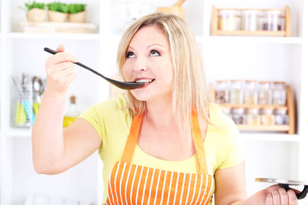 Happy smiling woman in kitchen preparing for healthy meal photo