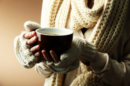 Female hands with hot drink, on color  Stock Photo