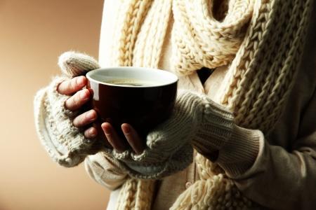 sueteres: Manos femeninas con la bebida caliente, sobre el color Foto de archivo