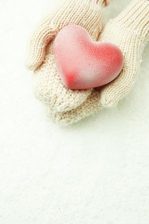 the mittens: Manos femeninas en guantes con el coraz�n rojo, primer plano