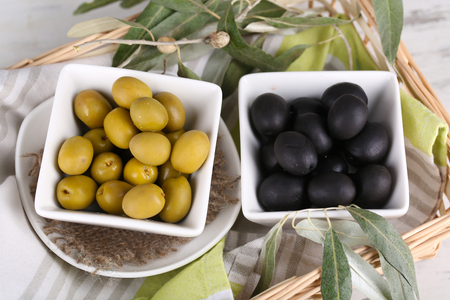 Olives in bowls with branch on napkin in basket close-up photo