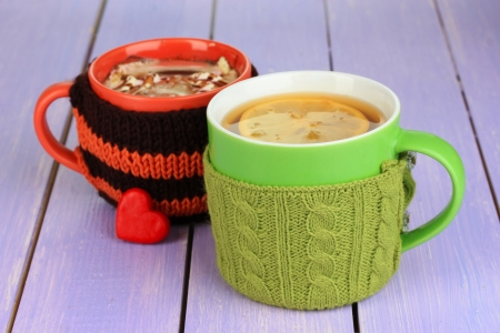 Cups with knitted things on it on wooden table close up photo