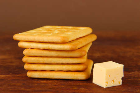 Delicious crackers with cheese on wooden table on brown  photo