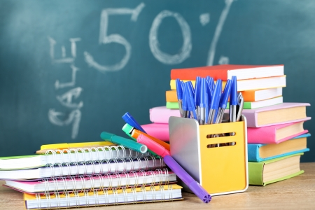 studing: Office supplies on table on school board background
