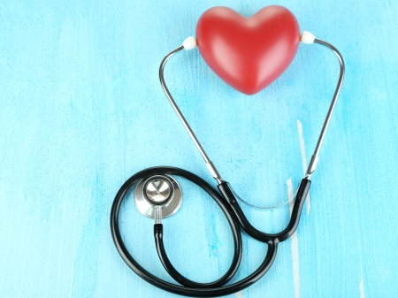 Stethoscope and heart on wooden table close-up Stock Photo