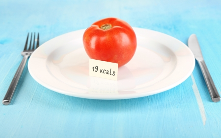 Calorie content of tomato on plate on wooden table close-up