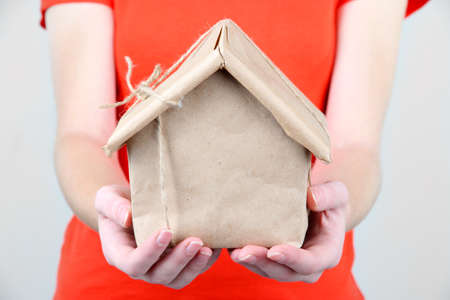 Woman hands holding a house wrapped in brown kraft paper photo