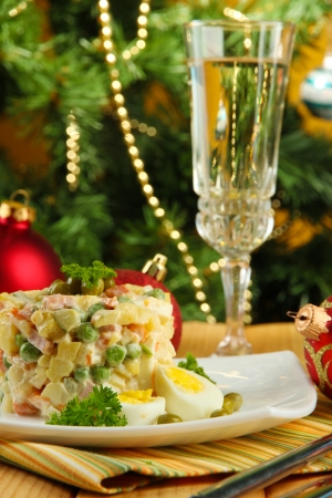 Russian traditional salad Olivier, on color napkin, on wooden  table, on bright background photo