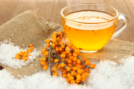 Branches of sea buckthorn with tea and sackcloth on wooden background Stock Photo - 23113960
