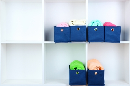 Blue textile boxes with towels in white shelves  photo