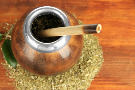 mate infusion: Calabash and bombilla with yerba mate on wooden background