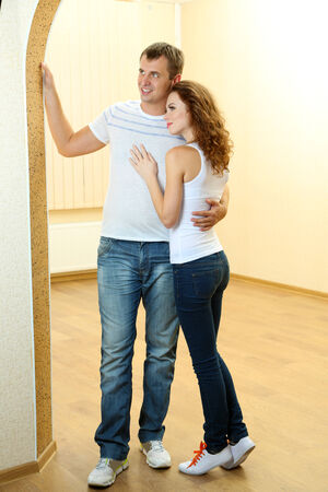 Young couple in new house on room background Stock Photo