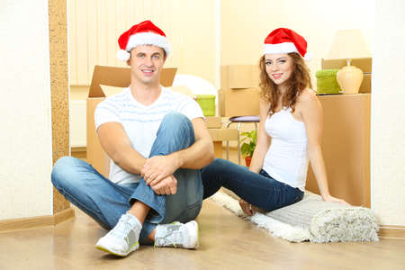 Young couple with boxes in new home celebrating New Years Stock Photo