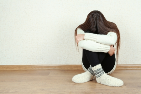 Sad woman sitting on floor near wall Stock Photo - 23114352