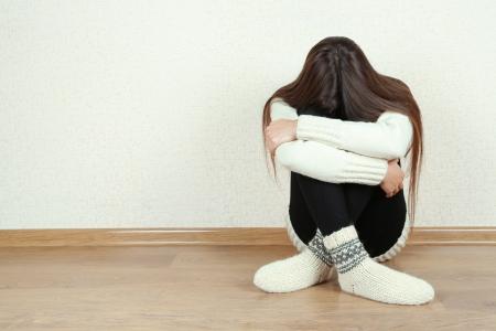 pullovers: Sad woman sitting on floor near wall Stock Photo