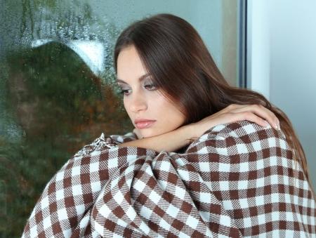 mujer llorando: Mujer triste sola que se sienta en la ventana