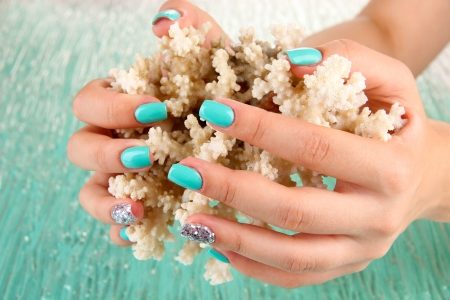 Beautiful woman hands with blue manicure holding coral, on color background