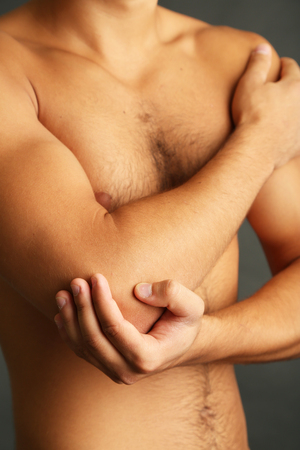 naked body: Young man with hand pain on grey background