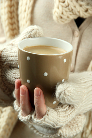 coffee mug: Female hands with hot drink, close-up