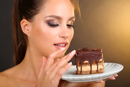 glutton: Portrait of beautiful young girl with chocolate cupcake on brown background