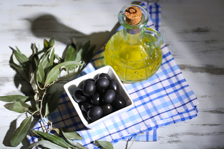 Olives in bowl with branch on sackcloth on wooden board on table Stock Photo - 23142053