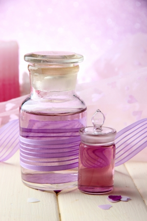 Glass bottles with color essence, on light background photo