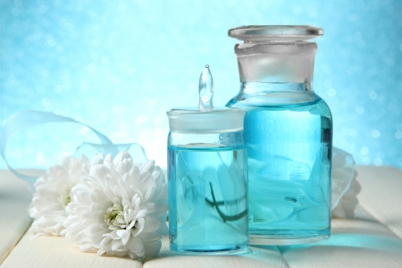 Glass bottles with color essence, on wooden table, on blue background