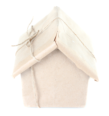 House wrapped in brown kraft paper, isolated on white photo