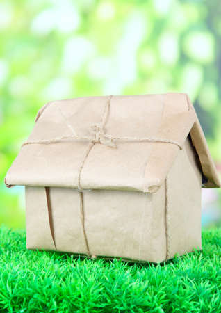 House wrapped in brown kraft paper, on green grass, on nature background photo