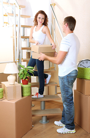 Young couple with boxes in new home on staircase