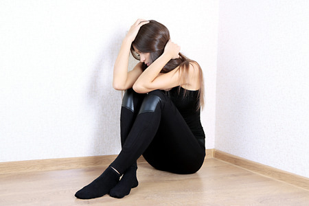 Lonely sad woman sitting on floor near wall Stock Photo