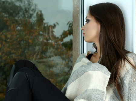 Lonely sad woman looking through window Stock Photo - 24340313