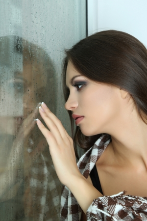 Lonely sad woman looking through window Stock Photo - 24340314