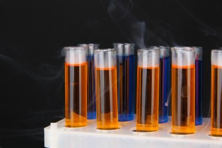 milliliters: Laboratory test tubes on black background
