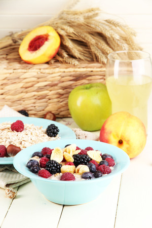 Oatmeal in plates with berries on napkins on wooden table on bright background photo