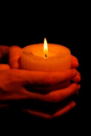 sacramentale: Masterizzazione di candela in mano isolato su fondo nero