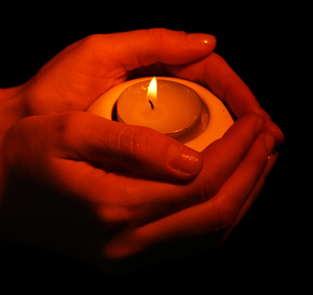 sacramental: Burning candle in hands isolated on black Stock Photo