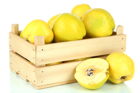Sweet quinces in wooden box isolated on white photo