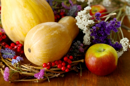 Pumpkin in wreath of dry branches with flowers and viburnum on wooden table close-up photo